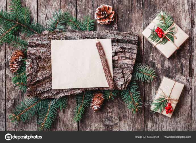 Christmas letter on wooden background with Christmas gifts, bark texture, pencil, Fir branches, pine cones, red decorations. Xmas and Happy New Year card. Flat lay, top view